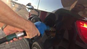 Χέρι που ξαναγεμίζει το αυτοκίνητο με τα καύσιμα ανεφοδιάστε σε καύσιμα το σταθμό Ανεφοδιασμός σε καύσιμα αυτοκινήτων στο πρατήρι απόθεμα βίντεο