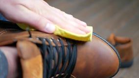 Χέρι που ξεσκονίζει τα καφετιά παπούτσια δέρματος με το κίτρινο κουρέλι απόθεμα βίντεο