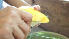 Χέρι που ξεφλουδίζει το ώριμο μάγκο στο ταϊλανδικό ύφος φιλμ μικρού μήκους