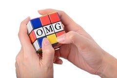Χέρι που παίζει τον τετραγωνικό γρίφο για να είναι OMG καλά - γνωστή έκφραση ο Στοκ Φωτογραφία
