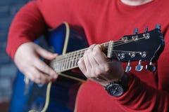 χέρι που παίζει το λαϊκό σχέδιο δράσης κιθάρων Στοκ Φωτογραφίες