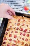 Χέρι που παίρνει ένα κομμάτι της γλυκιάς σπιτικής πίτας κερασιών Στοκ Εικόνα