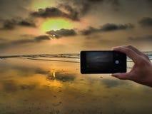 Χέρι που παίρνει τη φωτογραφία ενός ηλιοβασιλέματος παραλιών με το smartphone στοκ εικόνα