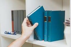 Χέρι που παίρνει το βιβλίο από το ράφι Στοκ φωτογραφία με δικαίωμα ελεύθερης χρήσης