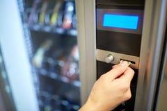 Χέρι που παρεμβάλλει το ευρο- νόμισμα στην αυλάκωση μηχανών πώλησης Στοκ εικόνα με δικαίωμα ελεύθερης χρήσης