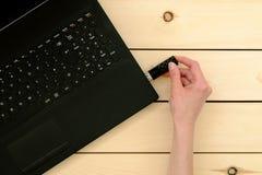 Χέρι που παρεμβάλλει usb το ραβδί μνήμης στο φορητό προσωπικό υπολογιστή Στοκ Εικόνες