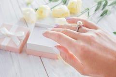 Χέρι που περιβάλλεται θηλυκό με τα λουλούδια που φορούν ένα δαχτυλίδι με το μαργαριτάρι πρόταση Στοκ Φωτογραφία