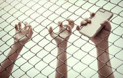 Χέρι που πιάνει το κλουβί πλέγματος Ο φυλακισμένος θέλει την ελευθερία Στοκ Φωτογραφία