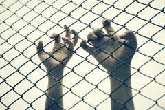 Χέρι που πιάνει το κλουβί πλέγματος Ο φυλακισμένος θέλει την ελευθερία Στοκ φωτογραφία με δικαίωμα ελεύθερης χρήσης