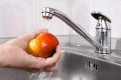 Χέρι που πλένει ένα μήλο Στοκ Εικόνες