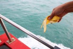 Χέρι που ρίχνει τα σκουπίδια στη θάλασσα από τη βάρκα στοκ εικόνες με δικαίωμα ελεύθερης χρήσης
