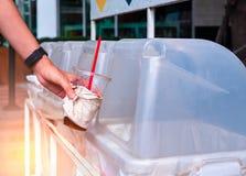 Χέρι που ρίχνει το κενό πλαστικό φλυτζάνι καφέ στο δοχείο ανακύκλωσης στοκ εικόνες