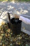 Χέρι που ρίχνει το πλαστικό μπουκάλι στα απορρίμματα Στοκ Εικόνες