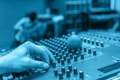 Χέρι που ρυθμίζει την ακουστικούς μουσική και τον ήχο αναμικτών Στοκ Φωτογραφία