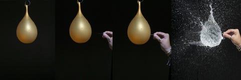 Χέρι που σπάζει ένα μπαλόνι με μια βελόνα στοκ φωτογραφία