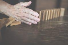 χέρι που σταματά την επίδραση συνεχούς ντόμινο που ανατρέπεται η γυναίκα προστατεύει Στοκ φωτογραφίες με δικαίωμα ελεύθερης χρήσης