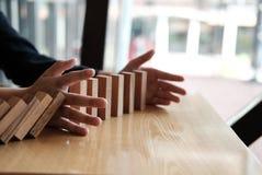 χέρι που σταματά την επίδραση συνεχούς ντόμινο που ανατρέπεται busineeman δημόσιες σχέσεις Στοκ φωτογραφία με δικαίωμα ελεύθερης χρήσης