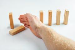 Χέρι που σταματά την πτώση ντόμινο Στοκ Εικόνα