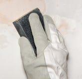 Χέρι που στρώνει με άμμο τον τοίχο με ένα στρώνοντας με άμμο σφουγγάρι Στοκ Εικόνα