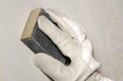 Χέρι που στρώνει με άμμο τον τοίχο με ένα στρώνοντας με άμμο σφουγγάρι Στοκ Εικόνες