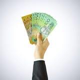 Χέρι που συγκεντρώνει τα χρήματα, αυστραλιανοί λογαριασμοί δολαρίων (AUD) Στοκ Φωτογραφία