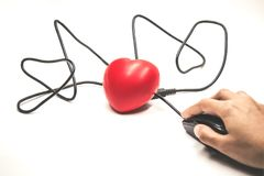 Χέρι που τοποθετεί στο μαύρο ποντίκι που που συνδέει με την κόκκινη καρδιά Στοκ εικόνες με δικαίωμα ελεύθερης χρήσης