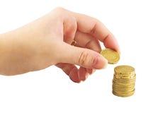 Χέρι που τοποθετεί το νόμισμα στη στοίβα χρημάτων Στοκ Εικόνες