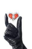 Χέρι που φορά τη μαύρη καρδιά εκμετάλλευσης γαντιών δέρματος Στοκ Φωτογραφία