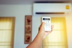 Χέρι που χρησιμοποιεί έναν τηλεχειρισμό στον ενεργοποιώντας κλιματισμό στο σπίτι στοκ εικόνα