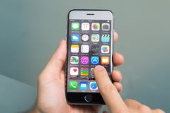 Χέρι που χρησιμοποιεί τα διάφορα apps στη Apple iPhone6 Στοκ Φωτογραφία