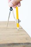 Χέρι που χρησιμοποιεί τα ξύλινα έπιπλα σχεδίου διαιρετών Στοκ Εικόνα