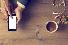 Χέρι που χρησιμοποιεί την τηλεφωνική άσπρη οθόνη στο ξύλινο υπόβαθρο στοκ εικόνες