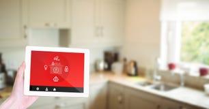Χέρι που χρησιμοποιεί το έξυπνο σπίτι app στην κουζίνα Στοκ φωτογραφία με δικαίωμα ελεύθερης χρήσης
