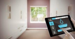 Χέρι που χρησιμοποιεί το έξυπνο σπίτι app στον υπολογιστή ταμπλετών Στοκ Εικόνες