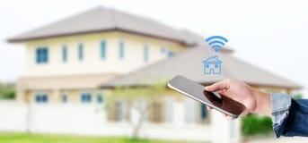 Χέρι που χρησιμοποιεί το έξυπνο τηλέφωνο πέρα από το υπόβαθρο σπιτιών θαμπάδων, έξυπνο σπίτι ομο στοκ φωτογραφίες με δικαίωμα ελεύθερης χρήσης