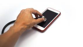 Χέρι που χρησιμοποιεί το στηθοσκόπιο για να ελέγξει το smartphone στοκ φωτογραφίες με δικαίωμα ελεύθερης χρήσης