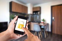 Χέρι που χρησιμοποιεί το smartphone από app το έξυπνο σπίτι σε κινητό Στοκ εικόνα με δικαίωμα ελεύθερης χρήσης