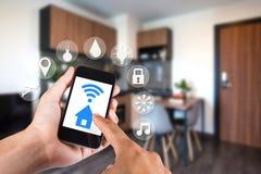 Χέρι που χρησιμοποιεί το smartphone από app το έξυπνο σπίτι σε κινητό Στοκ Εικόνες