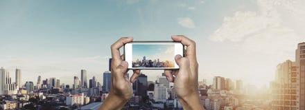 Χέρι που χρησιμοποιεί το smartphone που παίρνει τη φωτογραφία της πόλης της Μπανγκόκ στην ανατολή στοκ φωτογραφία