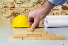 χέρι που χτίζει έναν τοίχο σε λίγα ξύλινοι φραγμοί στοκ εικόνα