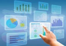 Χέρι που ωθεί στα διαγράμματα διαγραμμάτων διεπαφών οθόνης αφής και τα επιχειρησιακά οικονομικά σύμβολα Στοκ Φωτογραφία