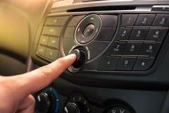 Χέρι που ωθεί το κουμπί δύναμης για να ανοίξει το στερεοφωνικό συγκρότημα αυτοκινήτων Στοκ εικόνες με δικαίωμα ελεύθερης χρήσης