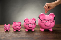 Χέρι προσώπων που παρεμβάλλει το νόμισμα σε Piggybank Στοκ Εικόνες