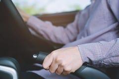 Χέρι προσώπων που τραβά handbrake το μοχλό στο αυτοκίνητο για την ασφάλεια σταθμεύοντας στοκ εικόνες