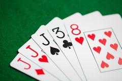 Χέρι πόκερ των καρτών παιχνιδιού στο πράσινο ύφασμα χαρτοπαικτικών λεσχών Στοκ Εικόνα