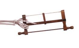 Χέρι σκελετών που κρατά το ξύλινο πριόνι Στοκ φωτογραφία με δικαίωμα ελεύθερης χρήσης