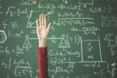 Χέρι σπουδαστών επάνω πίσω από τον πράσινο πίνακα κιμωλίας Στοκ φωτογραφία με δικαίωμα ελεύθερης χρήσης