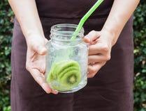 Χέρι στην εξυπηρέτηση του ποτηριού του παγωμένου ποτού σόδας ακτινίδιων Στοκ Εικόνες