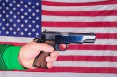Χέρι στο πυροβόλο όπλο με τη σημαία Στοκ εικόνες με δικαίωμα ελεύθερης χρήσης