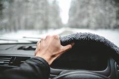Χέρι στο τιμόνι Οδήγηση στο χειμερινό δάσος Στοκ Φωτογραφίες